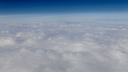 The beautiful cloudscape with clear blue sky. Panorama above white clouds as seen through window of an aircraft. A view from airplane window Reklamní fotografie - 125072443
