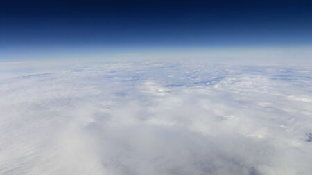 The beautiful cloudscape with clear blue sky. Panorama above white clouds as seen through window of an aircraft. A view from airplane window Reklamní fotografie - 125072446