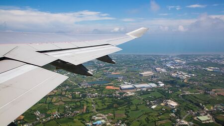 Traveling by air. Aerial view of a city at Taiwan Island. See the wing of the plane and the Taoyuan city in background as seen through an airplane window during the flight.