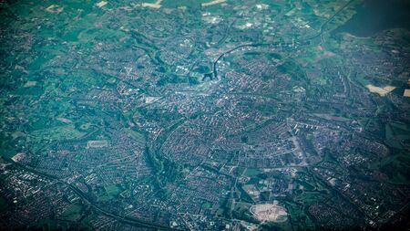 Aerial view of famous houses and roads of Amsterdam city from airplane window. Elevated view of cityscape. Wonderful top view of the capital at day. Plane flying above Netherlands