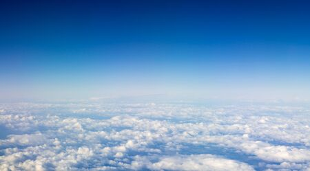 The beautiful cloudscape with clear blue sky. Panorama above white clouds as seen through window of an aircraft. A view from airplane window