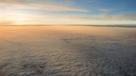 Aerial traveling. Wonderful view of the sky and clouds with the twilight from above, as seen through an airplane window. Morning mist. Flying at dusk or dawn. Fly through orange cloud and sun. Reklamní fotografie