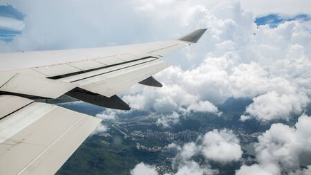 Aerial traveling. Flying through clouds. Ground under wing of an airplane go inside a cloud. View through an plane window of Hong Kong city with mountain. Aircraft fly.