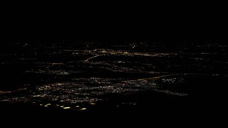 Lights of houses and roads of Amsterdam city top view from airplane window at night. Plane flying above Netherlands Reklamní fotografie