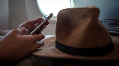 Young asian woman interior airplane. A passenger wear a hat on a plane using device phone during flight. Girl check the smartphone. Traveller sit down inside the plane using her phone device. Reklamní fotografie