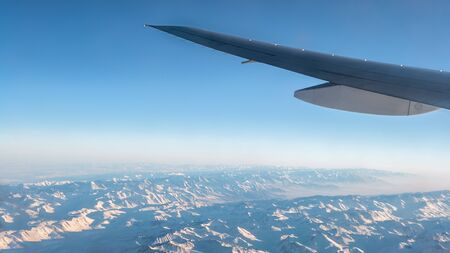 Traveling by air. Wonderful view of the Tian Shan snow mountains and clouds with blue sky from above in Central Asia, as seen through an airplane window
