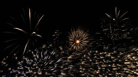 A beautiful Fireworks light up the sky with dazzling display on dark background. Celebration and anniversary concept. Firework show at night to celebrate the end of the holidays.