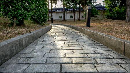 Paving stone road. Old pavement of square cobblestone sidewalk in Taipei. Garden patio in backyard stone brick pavers in Taiwan. Concrete paver block floor for background. Standard-Bild