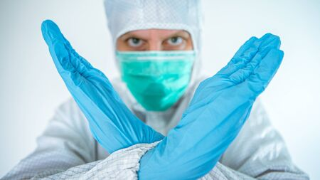 A caucasian man in a protective suit and mask shows the stop corona virus sign. Biological hazard. Epidemic of the Chinese coronavirus. Pandemic COVID-19. Medical and health care concept
