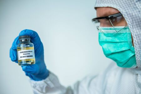 Doctor in protective suit and mask with a vaccine vial coronavirus. Preventive measures against Covid-19 infection. Epidemic virus outbreak concept. Medical and health care concept, Biological hazard