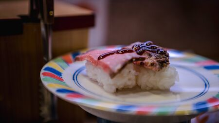 Sushi in a Japan restaurant. Traditional Kaitenzushi Japanese food. Shushi Go Round is a famous form of fast food in Asia, also known as sushi train.