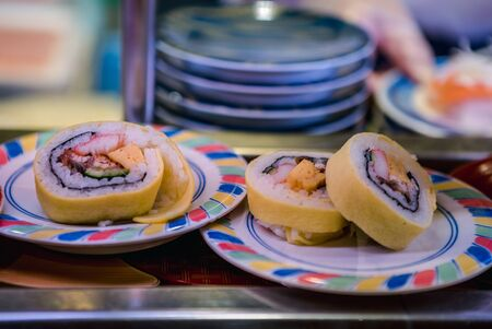 Sushi on conveyor belt in a Japan restaurant. Traditional Kaitenzushi Japanese food. Shushi Go Round is a famous form of fast food in Asia, also known as sushi train.