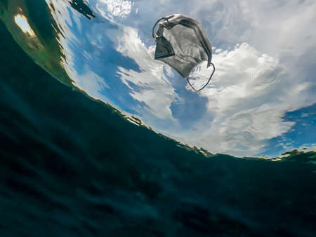 Protective mask discarded and thrown on the ocean. Abandoned facemask floating underwater of the sea. Used surgical masks for protection the coronavirus Covid-19. 免版税图像 - 151121549