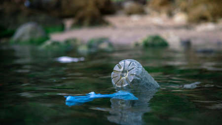 Coronavirus polluting the environment. The waves wash up old used medical mask waste, plastic bottle and gloves. Protective equipment get into the water, they pose a threat to marine life.