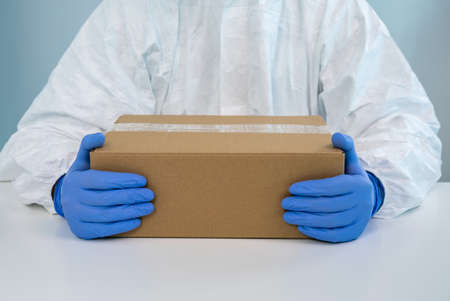 A nurse in a protective suit shows a box with both hands in a hospital. The healthcare worker receives medical supplies to fight Coronavirus Covid 19. Doctor wearing a PPE and gloves Foto de archivo