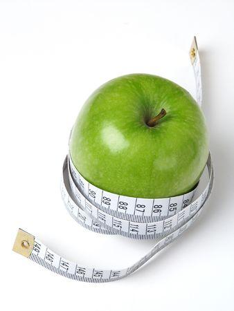 Grüner Apple mit Klebebandmaß. Lizenzfreie Bilder