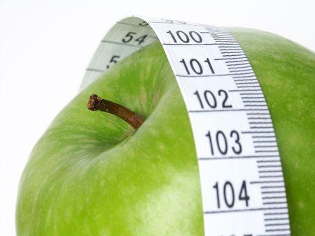 Grüner Apple mit Klebebandmaß. Standard-Bild