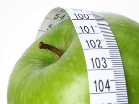 Green Apple with tape measure. Stock Photo