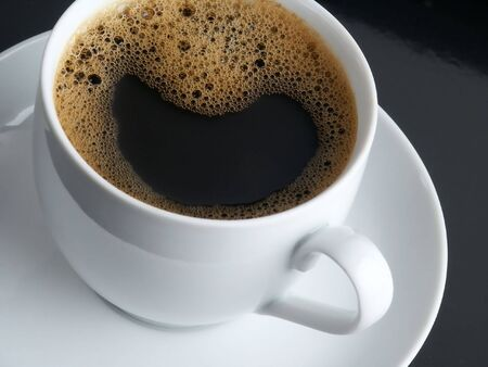 Fresh Black Coffee with Mousse. White Cup. Black Background.
