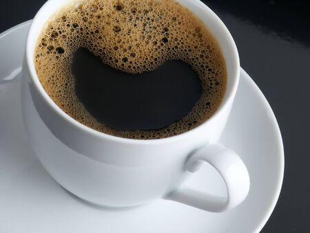 Frischer Kaffee mit Mousse. White Cup. Schwarzem Hintergrund.