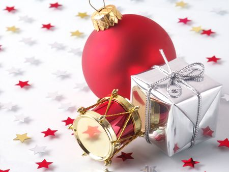 Christmas Decorations: Drum, Gift & Glass Ball with Star Confetti in background.