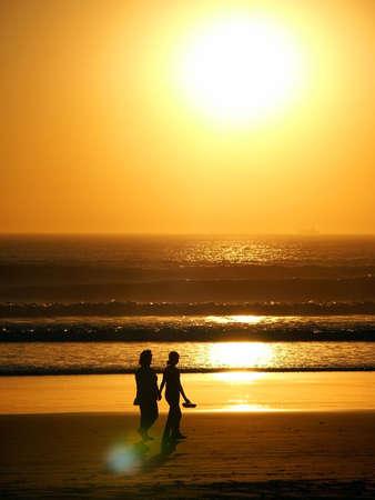 Couple walking and watching sunset.