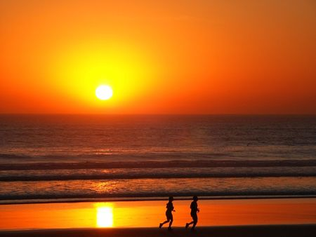 Couple running down the beach with bloody sunset in background.