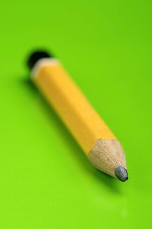 A yellow Pencil in closeup view. Green background. Soft focus. photo