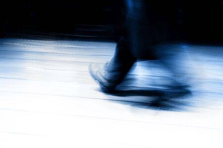Ein Bewegungsunschärfe Zusammenfassung einer Man Walking in Eile. Abend. Blauer Ton.