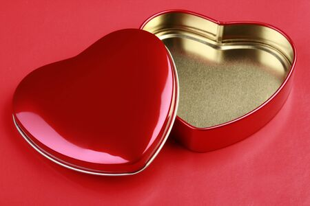Empty Heart-shaped Tin on red background. photo