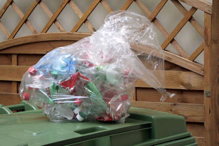Squeezed plastic Bottles in a plastic Bag lie on Dustbin. photo