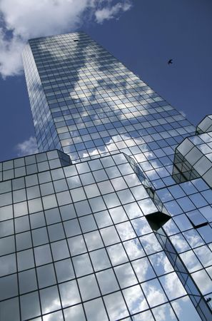 Blue sky and clouds reflected in the glass building in Warsaw (Poland).