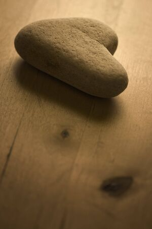 Heart shaped Stone on the Table. Retro style warm light and soft focus view. Stock Photo - 4338201