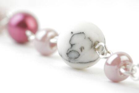 Fragment der Halskette mit farbigem Marmor und Perlen auf einem weißen Hintergrund. Weichzeichnungseffekt gesehen.
