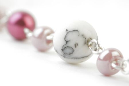 Fragment of Necklace with coloured and Marble Beads on a white background. Soft focus view. Stock Photo