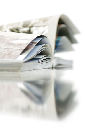 Soft focus view of opened color magazine with reflection. Close-up. Stock Photo