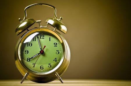 orologi antichi: Old fashioned metallo sveglia su sfondo marrone.