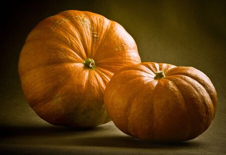 Two Pumpkins on brown background. Natural old style.