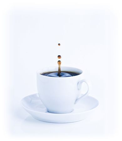 A cup of coffee with a splash of drops in the morning blue mood tones. Stock Photo