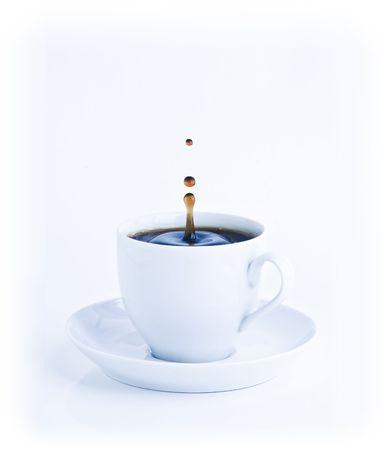 Eine Tasse Kaffee mit einem Schuss der Tropfen in den Morgen blau Stimmung Tönen. Lizenzfreie Bilder