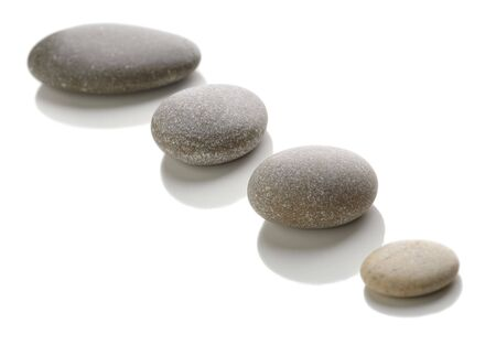 Four stones arranged in a straight line white background. photo