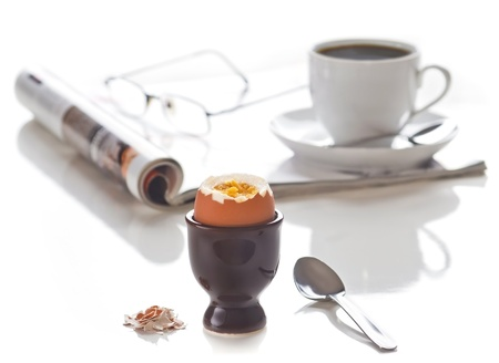 Breakfast. Egg with coffee. Focus on the egg. Isolated on white. photo