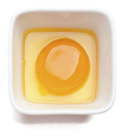 Egg yolk in square cup. Isolated on a white background.  photo