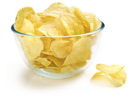 Heap of fried potato chips in glass bowl on white background.
