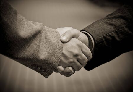 Closeup picture of businesspeople shaking hands, making an agreement. Against pavement.