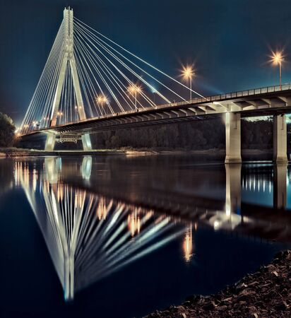 hdr: Night view of the new Swietokrzyski (Syrena) Bridge on Vistula river in Warsaw. Stock Photo