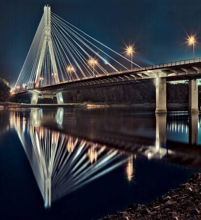 warsaw: Night view of the new Swietokrzyski (Syrena) Bridge on Vistula river in Warsaw. Stock Photo