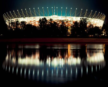 National Stadium in Warsaw at night with reflection in Vistula river.