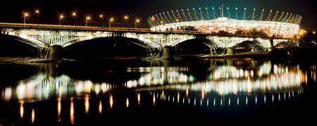 Poniatowski-Brücke und das Nationalstadion in Warschau in der Nacht mit Reflexion in Weichsel. Standard-Bild