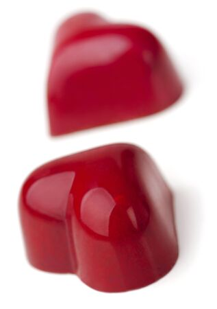 endorphines: Heart shaped Chocolate Pralines coated with burgundy glaze.  White background.